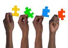 Homme tenant des morceaux de puzzle denteux Image stock