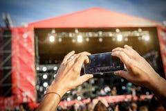 Homme tenant des smartphones dans les mains et la photographie Prise de la photo sur l'étape avant sur le summet Image libre de droits