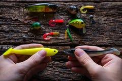 Homme tenant deux attraits pour pêcher avec la rotation sur la table Photo stock