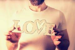 Homme tenant l'amour de mot au fond de mur Images stock