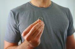 Homme tenant l'anneau de mariage Photographie stock
