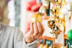 Homme tenant la babiole d'or de Noël au magasin Image libre de droits
