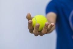 Homme tenant la balle de tennis Photographie stock libre de droits