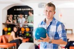 Homme tenant la boule de bowling dans le club Photos stock