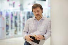 Homme tenant la bourse avec la monnaie fiduciaire russe Photographie stock