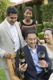 Homme tenant la bouteille et le verre de vin avec des amis en parc Photos libres de droits
