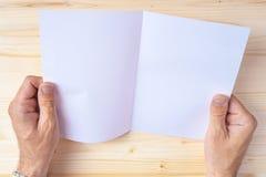 Homme tenant la brochure vide en tant que moquerie vers le haut de l'espace de copie Image stock