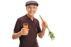 Homme tenant la carotte et le verre de jus Image libre de droits