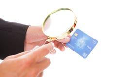 Homme tenant la carte de crédit et la loupe Image stock