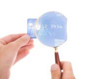 Homme tenant la carte de crédit et la loupe Photos libres de droits