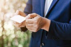 Homme tenant la carte de visite professionnelle de visite blanche Photographie stock libre de droits