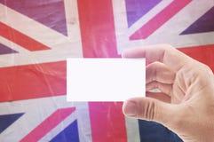 Homme tenant la carte de visite professionnelle vierge de visite contre le drapeau du Royaume-Uni Images stock