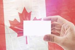 Homme tenant la carte de visite professionnelle vierge de visite contre le drapeau national de Canada Image stock