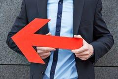 Homme tenant la flèche rouge vers la gauche Photographie stock