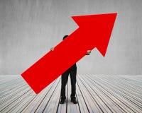 Homme tenant la flèche rouge vers le haut du signe Image stock