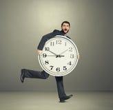 Homme tenant la grande horloge et le fonctionnement Photos stock