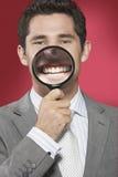 Homme tenant la loupe sur la bouche de sourire photos stock