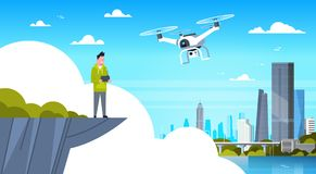 Homme tenant la mouche à distance de For Modern Drone de contrôleur au-dessus du fond de bâtiments de ville Images stock