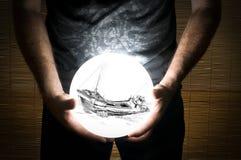 Homme tenant la sphère blanche avec une épave de bateau à l'intérieur Photographie stock