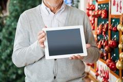 Homme tenant la Tablette de Digital au magasin de Noël Photographie stock