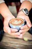 Homme tenant la tasse chaude de latte de café Photo libre de droits