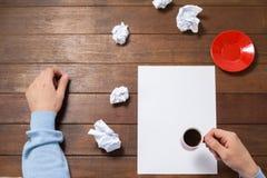 Homme tenant la tasse de café sur le papier Photos stock
