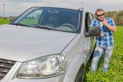 Homme tenant la voiture proche penchée sur la porte Photo libre de droits