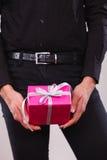 Homme tenant le boîte-cadeau rose actuel dans des mains Photographie stock