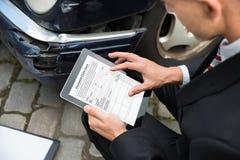 Homme tenant le comprimé numérique examinant la voiture endommagée Photo stock