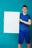 Homme tenant le conseil de présentation vide sur le bleu Photos stock