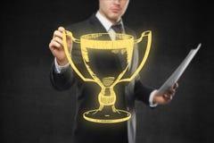 Homme tenant le croquis de la tasse du gagnant d'or Photo stock