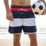 Homme tenant le football sur la plage photos libres de droits