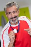 Homme tenant le gagnant de la médaille d'or en concurrence Image libre de droits