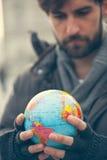 Homme tenant le globe image stock