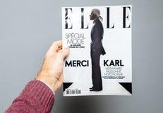 Homme tenant le magazine d'Elle comportant la mort de Karl Lagerfeld de couverture photographie stock
