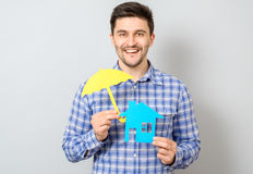 Homme tenant le modèle de la maison Concept pour l'assurance à la maison Photo libre de droits