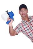 Homme tenant le pulvérisateur de peinture photos stock