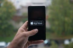 Homme tenant le smartphone avec le logo de magasin d'Apple APP avec le doigt sur l'écran Photos stock