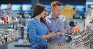 Homme tenant le téléphone intelligent et se dirigeant à l'autre téléphone qui est chez des mains de la femme Intérieur de magasin clips vidéos