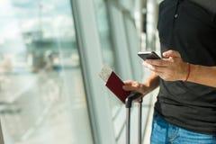 Homme tenant le téléphone portable, les passeports et l'embarquement Photo libre de droits