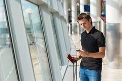 Homme tenant le téléphone portable, les passeports et l'embarquement Photos stock