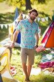Homme tenant le terrain de camping proche Photographie stock libre de droits