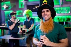 Homme tenant le verre et le sourire de bière Images stock