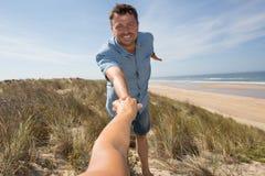 Homme tenant le woman& x27 ; main de s et conduite de lui sur l'océan extérieur Images stock