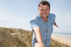 Homme tenant le woman& x27 ; main de s et conduite de lui sur l'océan extérieur Image stock