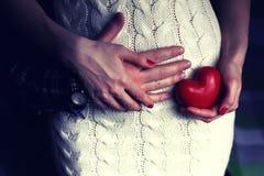 Homme tenant les femmes enceintes avec la forme de coeur Photo stock