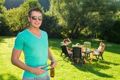 Homme tenant les pinces et la bouteille de vin à la réception en plein air Photos stock