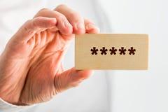 Homme tenant un bloc en bois avec 5 étoiles Image libre de droits