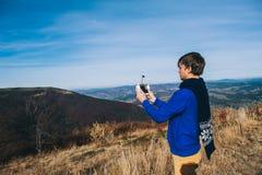 Homme tenant un bourdon pour la photographie aérienne Images stock
