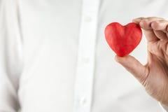 Homme tenant un coeur rouge romantique Photo stock